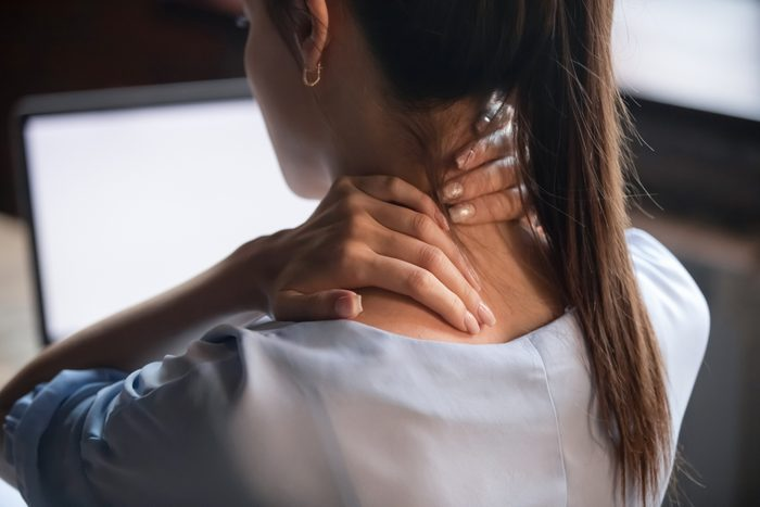 rear view close up of woman with neck pain