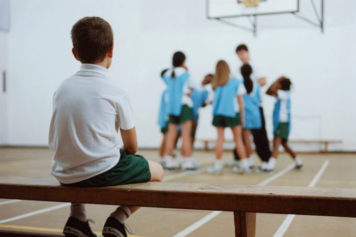 young boy sitting on bench watching basketball team play