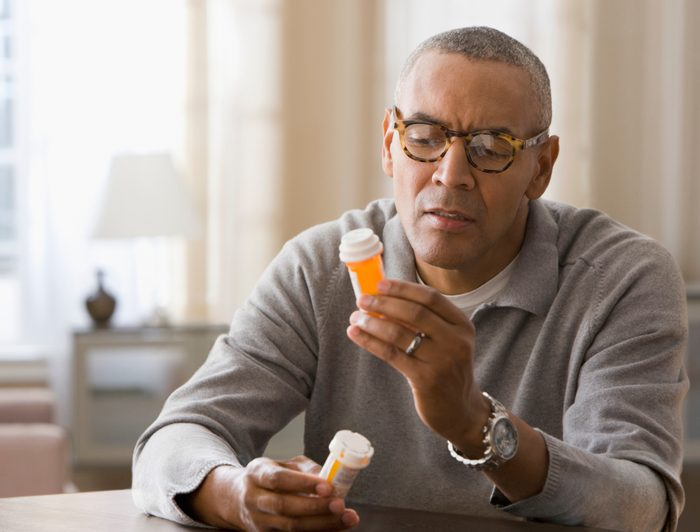man looking at prescription pill bottle