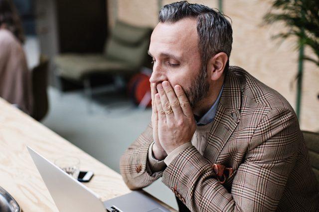 upset businessman looking at laptop
