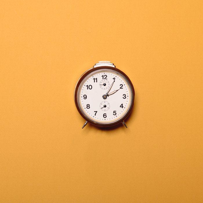 Vintage brown alarm clock on yellow ocher background - Trendy minimal flat lay concept