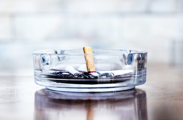 Cigarette butts and ashtray in a glass