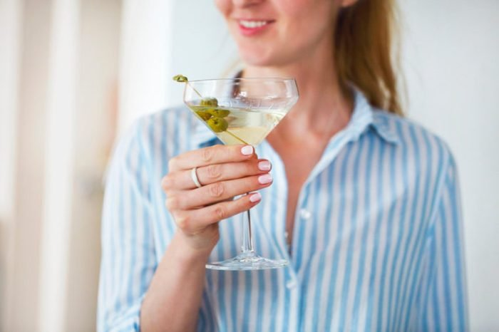 Woman holding glass with martini and green olives.