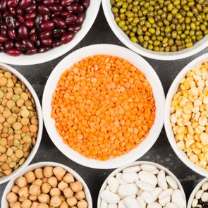 Assortment of beans (red lentil, green lentil, chickpea, peas, red beans, white beans, mix beans, mung bean) on gray background. Top view. Food background