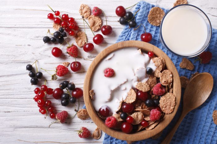 Cereal with milk and fresh berries in a wooden bowl.