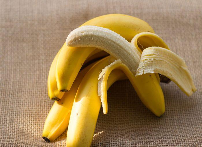 bunch of bananas and one peeled banana