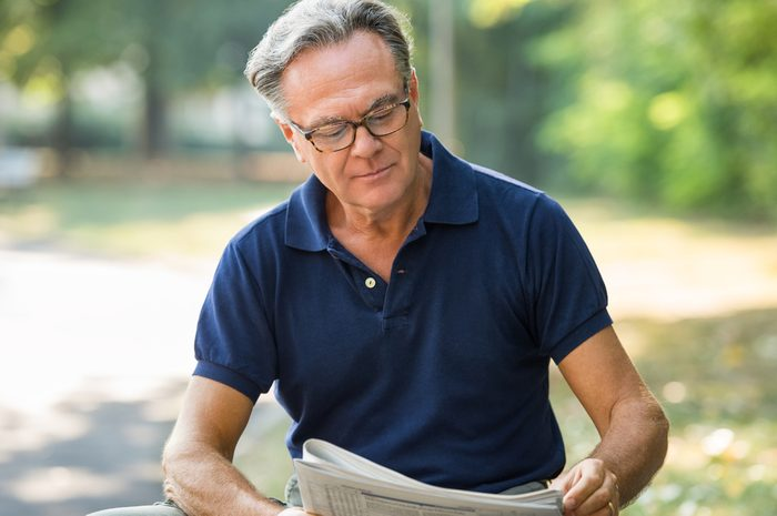 Senior man sitting at park and reading newspaper for aging brain