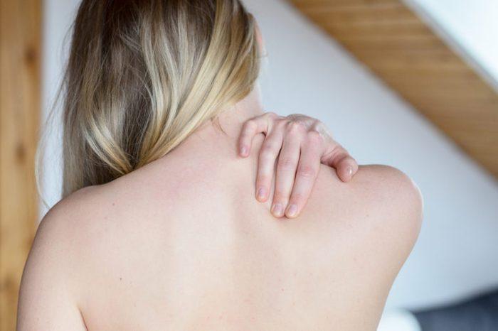 Woman rubbing upper back