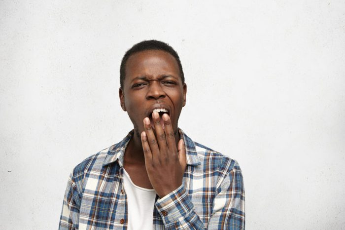 Young man covering mouth while yawning.