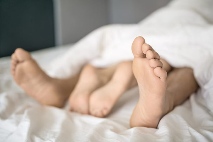 Barefoot legs of lovers under a blanket