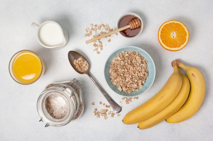 Oatmeal, milk, honey, orange, orange juice, bananas on a white countertop