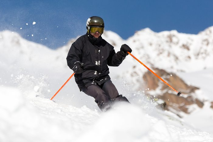 Male skier skiing in fresh snow on ski slope on a sunny winter day at the ski resort