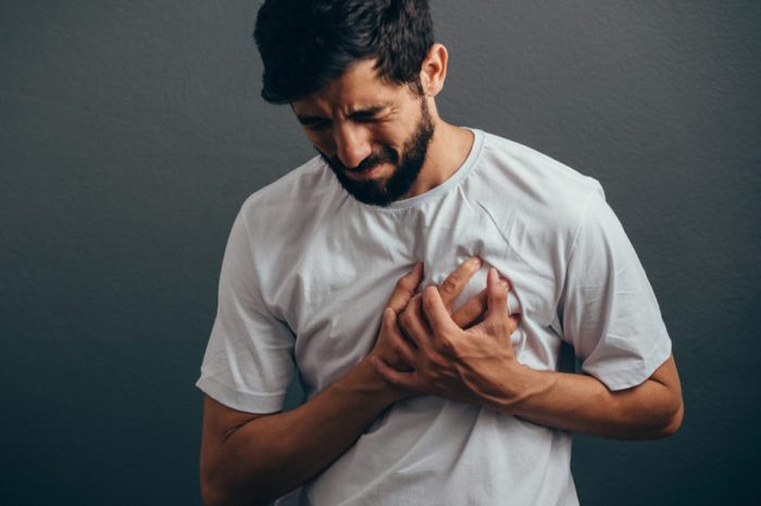 close up of man suffering from heart ache over gray background