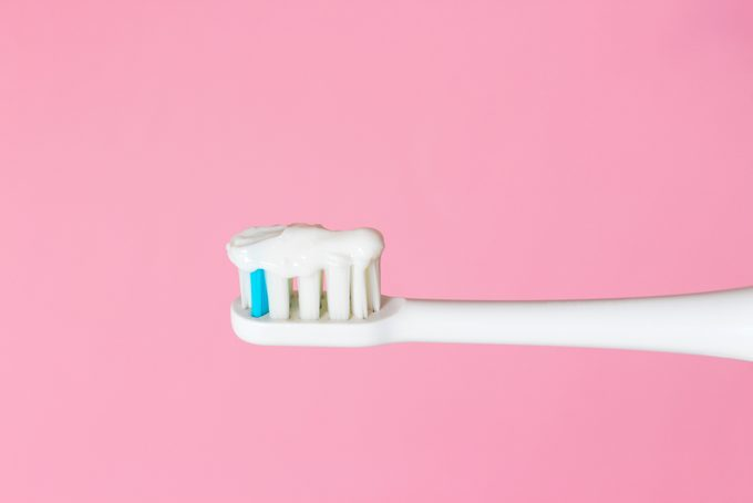 White electric toothbrush and toothpaste on pink background. The concept of good mouth hygiene. Close up.