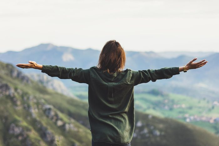 woman outdoors with arms outstretched