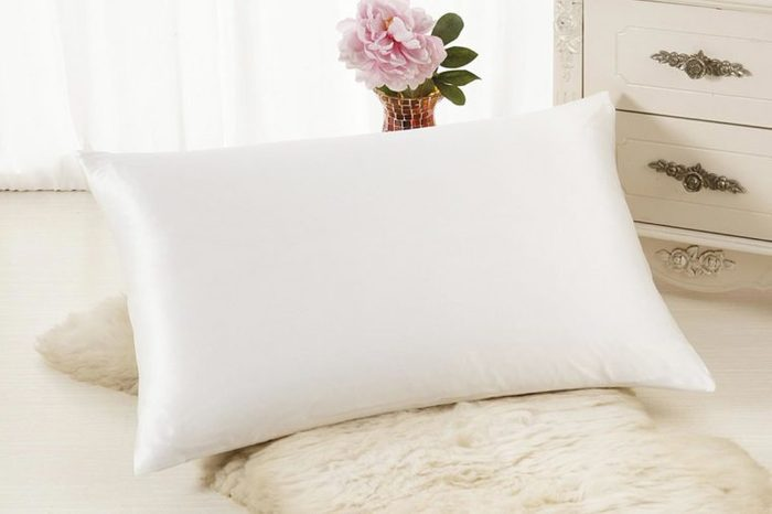 Silk white pillowcase in a bedroom.