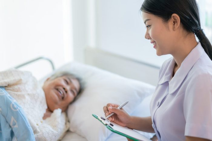 Asian nurse checking up the history of the disease elderly patient lying in bed. Nurse cares for a elderly woman.