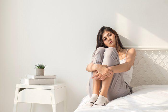 sad woman sitting on bed