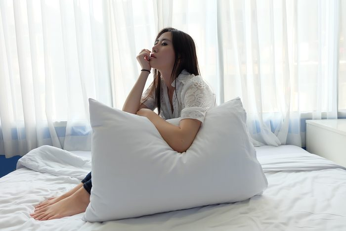 woman sitting in bed alone