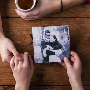 Unrecognizable man holding womans hand. Looking  at their photo. Couple