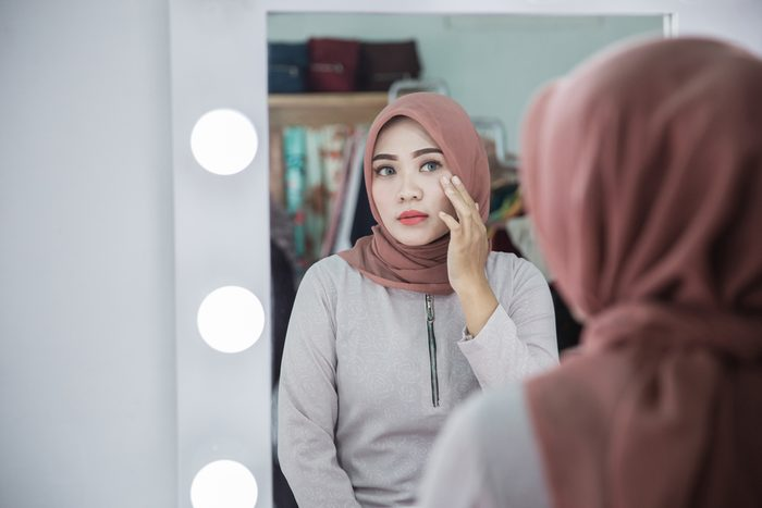 woman wearing makeup looking at herself in the mirror