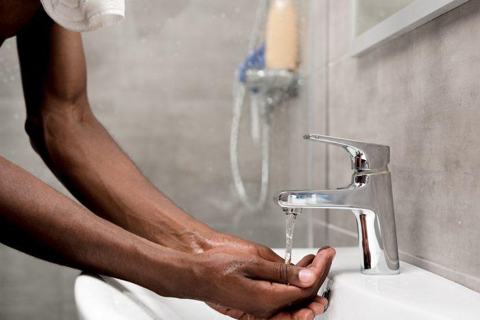 cropped shot of african american man washing in bathroom