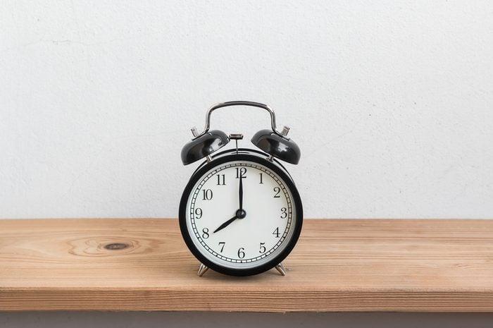 Vintage alarm clock on wood shelf ( alarm clock show 8 o`clock )