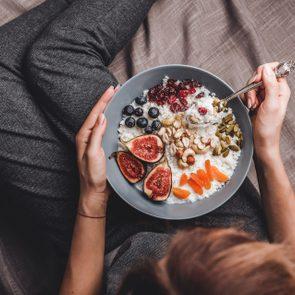 Woman in home clothes eating vegan Rice coconut porridge with figs, berries, nuts. Healthy breakfast ingredients. Clean eating, vegan food concept