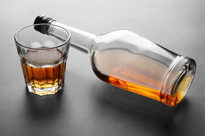 whiskey bottle on it's side next to a glass of whiskey