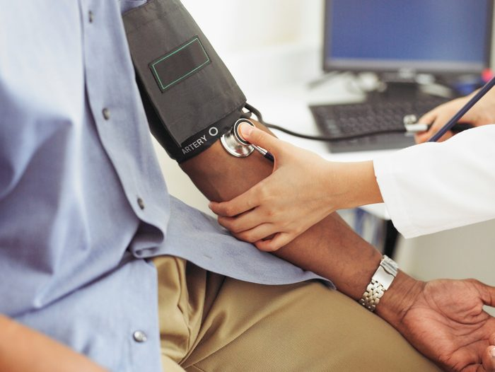 close up of doctor taking patient's blood pressure