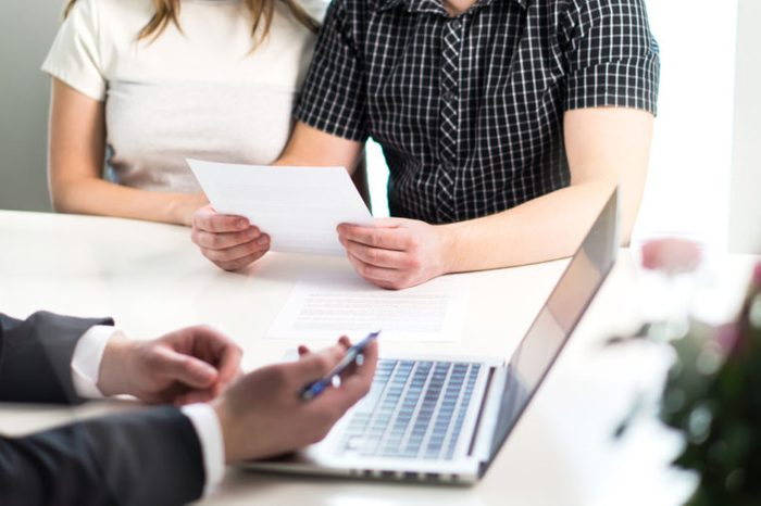 People having meeting about mortgage, bank loan, buying house, insurance or apartment rent. Woman, man and lawyer preparing prenupitial agreement in office. Person reading real estate paper contract.