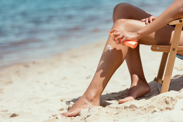 cropped image of woman applying sunscreen lotion on legs while sitting on deck chair on sandy beach