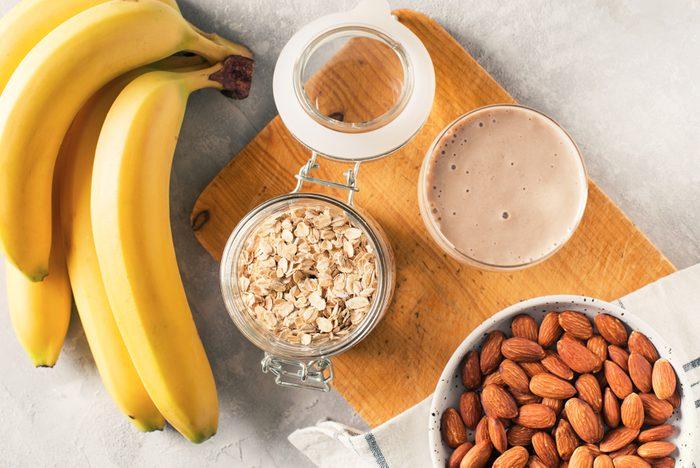 Healthy breakfast banana oatmeal almond milk on white background