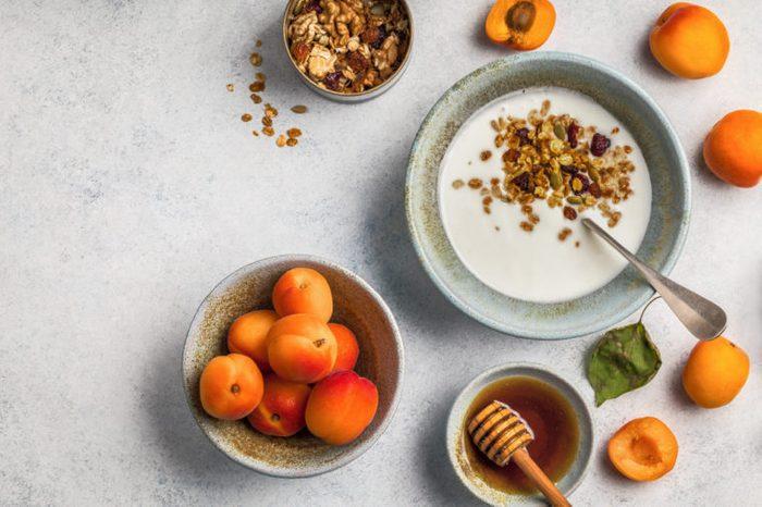 Healthy breakfast with yogurt, honey granola, fresh apricots.