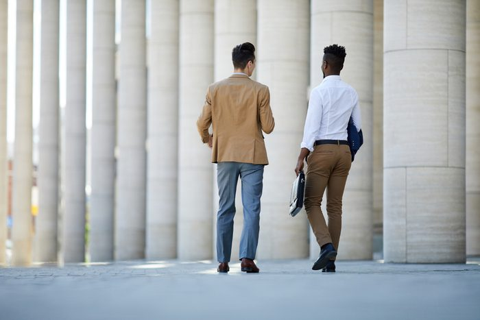 Two young intercultural businessmen in formalwear walking to work while having talk