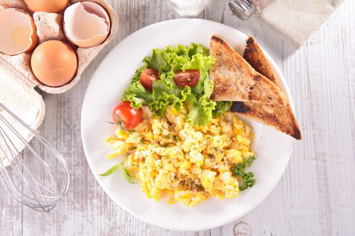 Breakfast meal of scrambled eggs, salad, and toast on a white table.