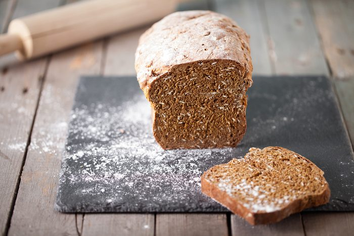 Fresh Irish soda bread with oat sliced on a slate cutting board Wooden background Copy space Selective focus
