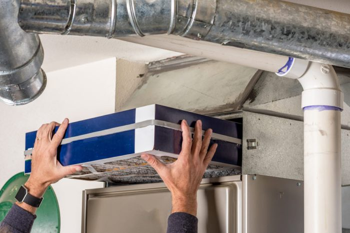 Person changing their home furnace air filter replacement