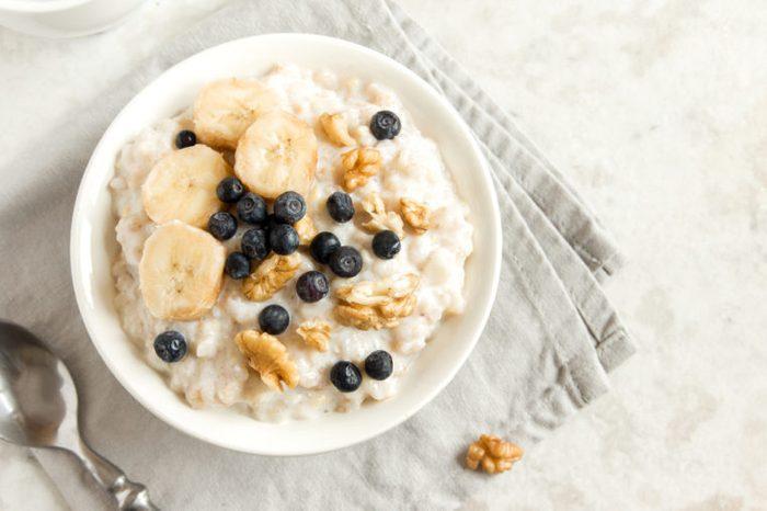 Oatmeal porridge with walnuts, blueberries and banana in bowl - healthy rustic breakfast