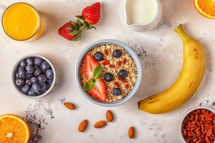 Healthy breakfast - a bowl of oatmeal, berries and fruit, orange juice, milk.
