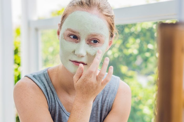 Spa Woman applying Facial green clay Mask. Beauty Treatments. Close-up portrait of beautiful girl applying facial mask.