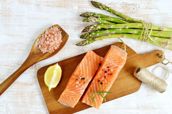 salmon fillets and lemon wedge with asparagus, pink salt, and twine