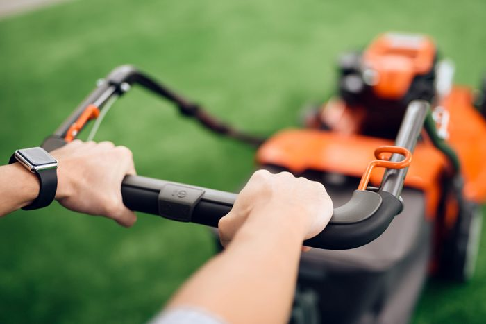 A man holds a lawn mower for the handle. He came to the tools store for gardening. He has a wristwatch on his hand.