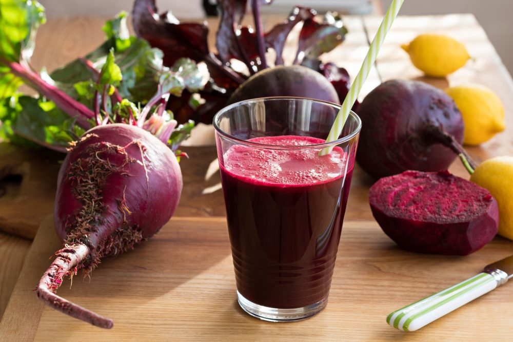 Stock image: Red beet juice in a glass on a wooden table with fresh beets and lemons in the background