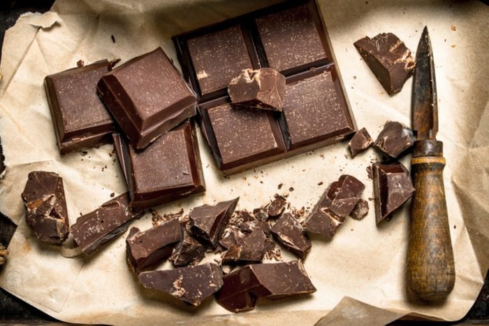 Chocolate squares and shavings with knife on paper