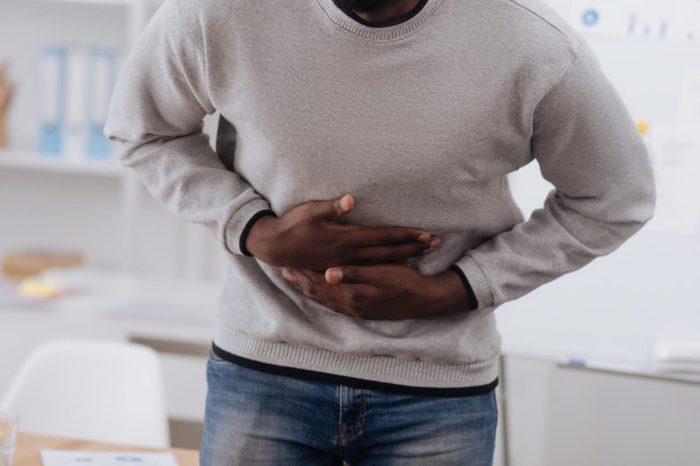 Black man in a sweater bent over and holding his stomach in pain
