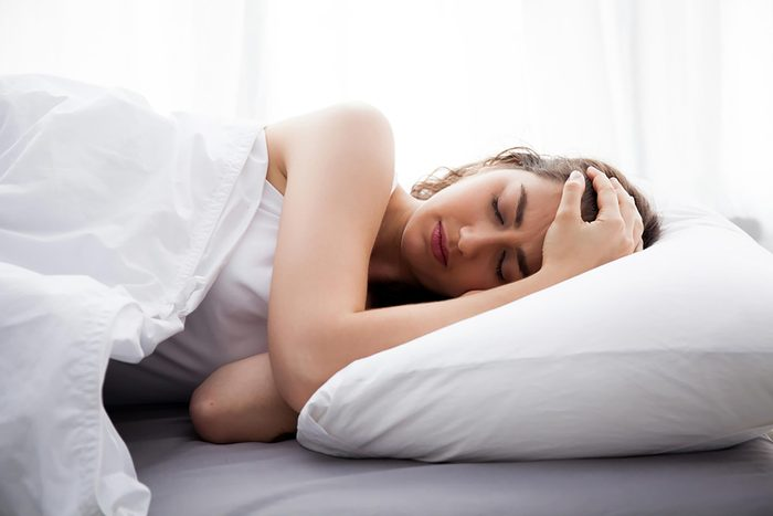 woman on her side in bed, holding her head