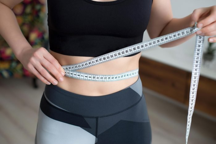 A young woman in a sportswear checking success of weight loss program with measuring tape in front of mirror at home.