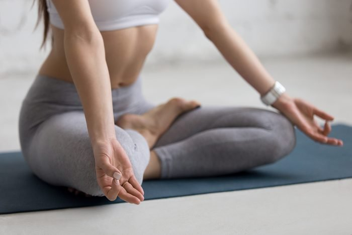 Beautiful young woman working out in loft interior, doing yoga exercise on blue mat, Sitting in Ardha Padmasana, Half Lotus Posture, meditating, breathing, close-up