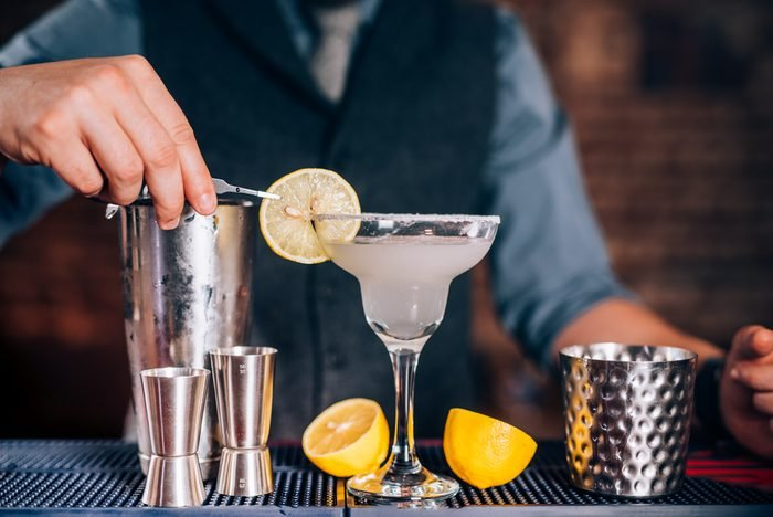 Bartender garnishing drink, pouring fresh lime margarita in fancy glass at restaurant
